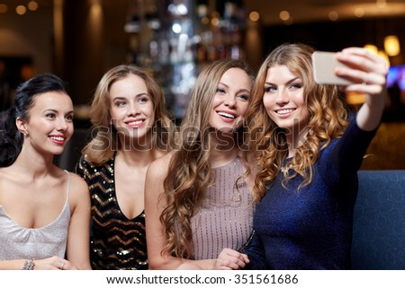 celebration, friends, bachelorette party, technology and holidays concept - happy women with smartphone taking selfie at night club - stock photo