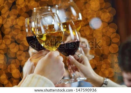 Celebration. Hands holding the glasses of champagne and wine making a toast. - stock photo