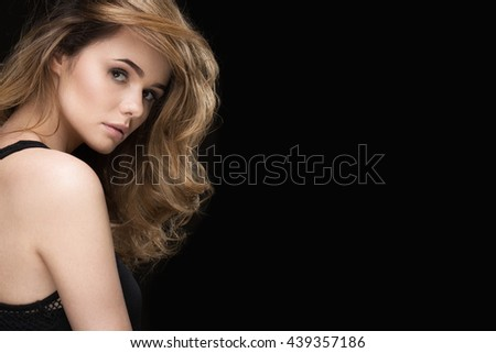 Celebration of beauty. Gorgeous young woman with massive curly hairstyle posing on black background looking to the camera confidently copyspace on the side