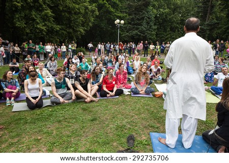 Celebration of Yoga in Minsk Gorky Park. People sit and engage in the gym mat in the park. Belarus, Minsk, June 21, 2015