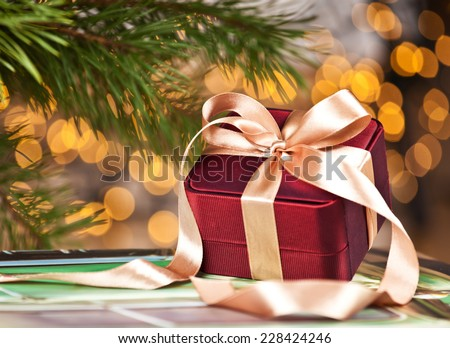Celebration theme with christmas gifts. Elegant gift box with ribbon in shiny gold night.  - stock photo