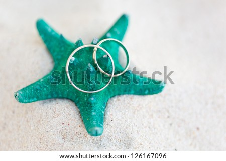 Celebration Valentine's day on beach, rings on starfish - stock photo