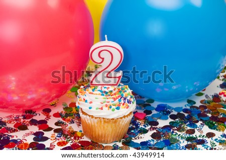 Celebration with balloons, confetti, cupcake, and number 2 candle.