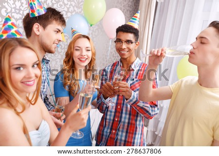 Celebration. Young people drinking champagne from high glasses and smiling celebrating birthday of their friend selective focus