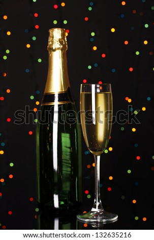 Celebratory champagne with wineglass on Christmas lights background