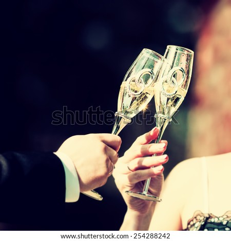 Celebratory glass of champagne in hand of bride,vintage - stock photo