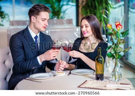 Celebratory supper for two. Romantic dinner in the restaurant. Young loving couple visit a restaurant and raised their glasses of wine and look out the window until the guy holding the hand of a woman - stock photo
