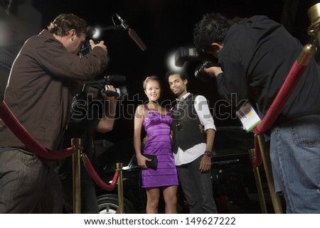 Celebrity couple being photographed at media event - stock photo