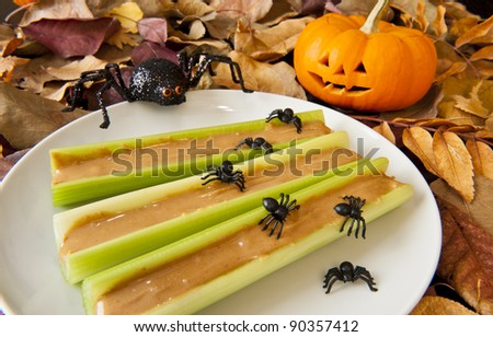 Celery sticks with peanut butter and Halloween spiders - stock photo
