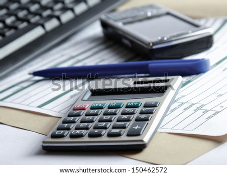 Cell phone and calculator near laptop - stock photo