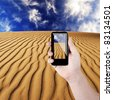 Cell phone in hand and desert view on sunny day - stock photo
