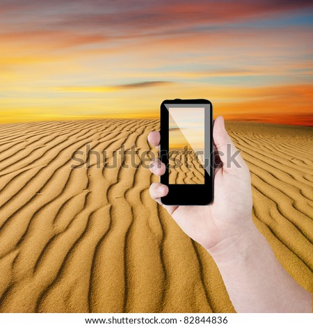 Cell phone in hand take photo of beautiful desert view - stock photo