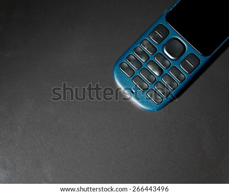 Cell phone keypad and a lot of copyspace on dark background. Old fashioned mobile phone of blue color and a lot of space for text   - stock photo