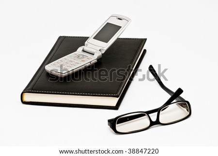 Cell phone on black agenda and glasses isolated on white