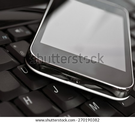 Cell phone on laptop keyboard - Business concept - stock photo