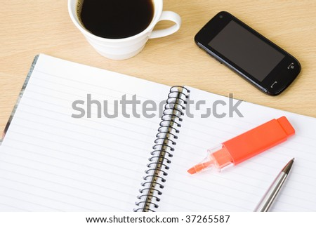 Cell phone with spiral notebook and cup of coffee arranged on office table - stock photo