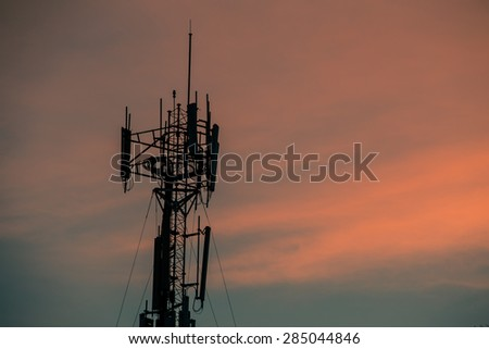 Cell site, Telecommunications radio tower or mobile phone base station with atop the antennas, dark silhouette with dusk sky background. - stock photo