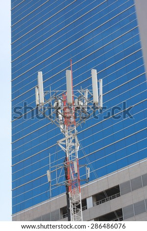 Cell site, Telecommunications radio tower or mobile phone base station with atop the antennas with building background. - stock photo