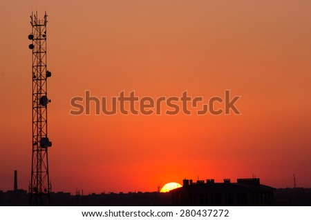 Cell tower and the city of construction on a background of red sunset - stock photo