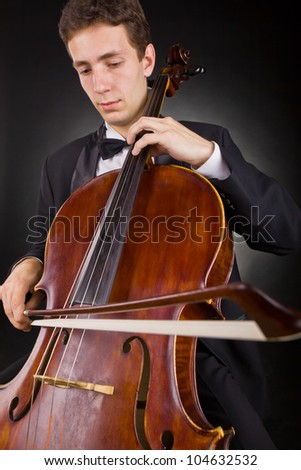 Cellist playing classical music on cello on black background. Focus on the cello - stock photo
