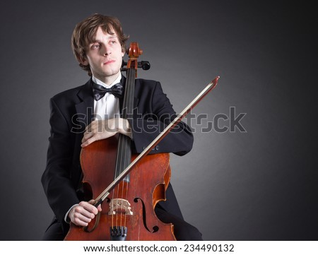 Cellist sits in thought with a musical instrument. - stock photo