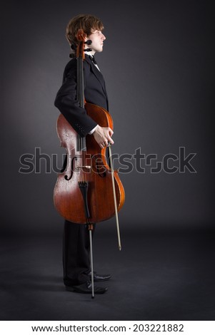 Cello musician standing with a dark background. - stock photo