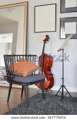 cello or violoncello musical instrument with wooden chair and pillow at home - stock photo