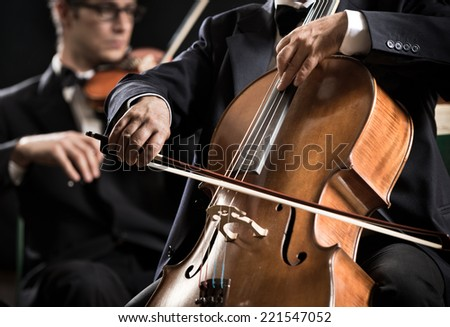 Cello professional player with symphony orchestra performing in concert on background. - stock photo