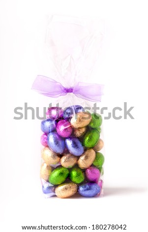 Cellophane bag of colourful chocolate mini easter eggs, with a bow round the top of the bag and a white background - stock photo