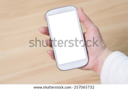cellphone in hand on wooden background - stock photo