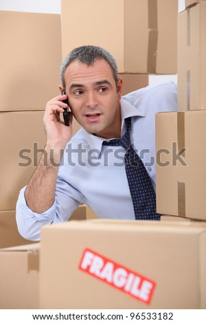 Cellphone user surrounded by boxes - stock photo