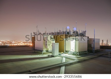 Cellular, Base Radio station on the roof of building at night time. - stock photo
