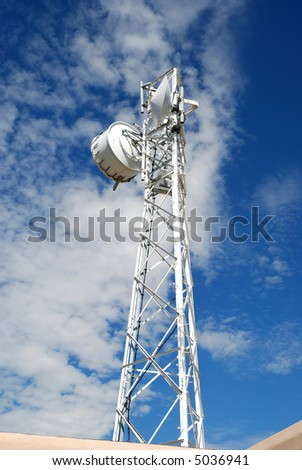 Cellular communication tower against a cloudy blue sky