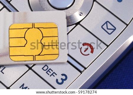 Cellular phone with a SIM card isolated on blue concepts of wireless communication - stock photo