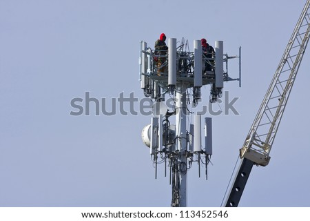 Cellular tower with workers present atop the antennas