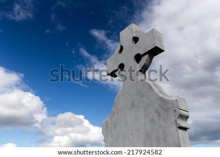 celtic cross in front of blue sky with clouds - stock photo