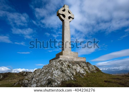 Celtic stone cross monument on a hill against a blue sky.