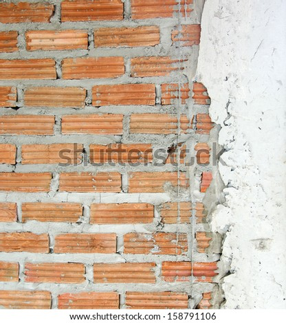 Cement plastered brick wall, unfinished to see the texture of the brick. - stock photo