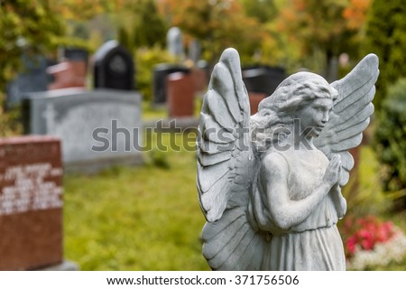 Cemetery Angel statue praying in front of several headstones on a graveyard in Fall, in a cemetary. - stock photo