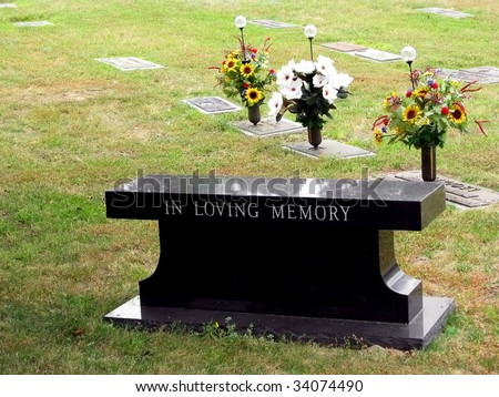 cemetery grave tombstone engraved in loving memory - stock photo