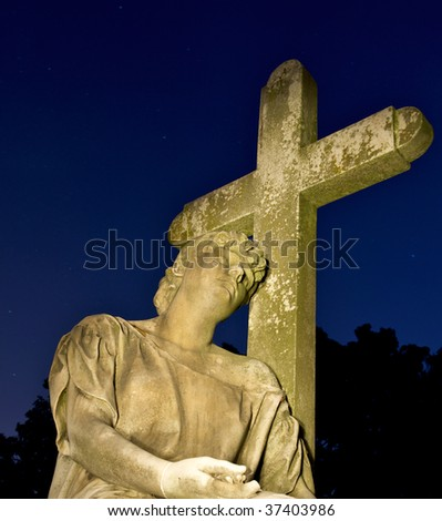 Cemetery headstone of a man resting his head against a cross surrounded by a dark blue night sky.