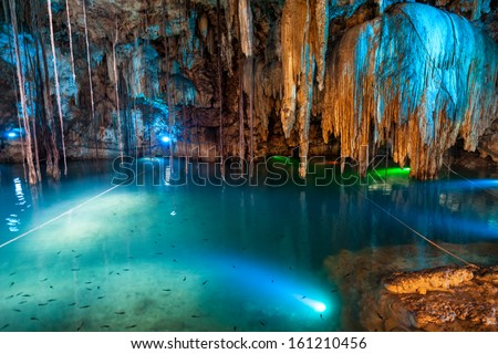Cenote Dzitnup near Valladolid, Mexico. lovely cenote with transparent turquoise waters and large stalactites - stock photo