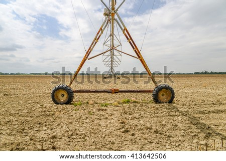 Center pivot irrigation system on a green field during a drought - stock photo