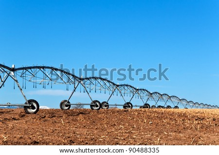 Center pivot irrigation system sitting idle waiting for the growing season next spring. - stock photo
