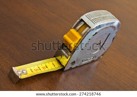Centimeter tape worn by long use on wooden board - stock photo