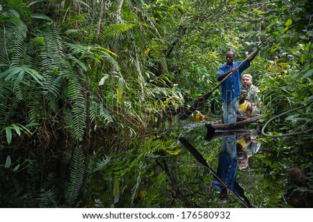 CENTRAL AFRICA JUNGLE, CONGO, AFRICA - SEPTEMBER 30, 2013 : White tourist photographer travels on a pirogue on the jungle of the central Africa. In 30 september, Congo Brazzaville, Africa - stock photo