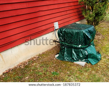 Central Air Conditioning Unit Covered for Winter - stock photo