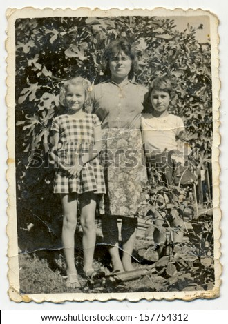 CENTRAL BULGARIA, BULGARIA - CIRCA 1955: the area Plovdiv - Woman hugging two unidentified children in the garden - Note: slight blurriness, better at smaller sizes - circa 1955