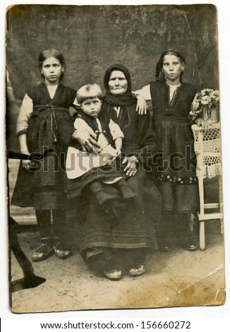 CENTRAL BULGARIA, BULGARIA, district Plovdiv - CIRCA 1930: Traditional family in period dress (here an old woman and two girls, one boy) - Note: slight blurriness, better at smaller sizes - circa 1930