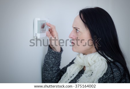 Central heating problems. Cold and unhappy woman struggling to turn heating temperature up on wall thermostat.